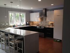 """I have heard the term """"Farm House Modern"""" and this kitchen looks to be an example.  Clean, shiny cabinets and stainless steel appliances are paired with what looks like a rough ledgestone backsplash and county counterstools."""