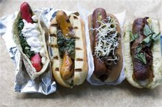 From left are these hot dogs: Greek spanakopita, Indian curry, taco and pizza.