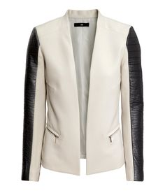 Black faux leather accent panels bring a rebellious touch to the sophisticated white fitted jacket. | Warm in H&M
