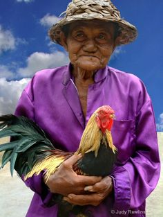 """The Prize Rooster © Judy R. Rawlinson who says: In Bali interior the women are responsible for ALL the work. They maintain the household, work the crops, construction, road work, etc. The men...fight cocks. This man is all dressed up on his way to """"work"""" with his prize rooster."""