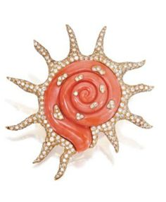Coral, diamond and gold swirl sun brooch.