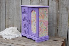 Upcycled vintage jewelry armoire. Wood, hand painted in purple with decoupage of flowers and paisley in purple, lavender and pink, with a protective clear coat. The door is decoupaged on the outside and inside, and opens to a mirror, necklace carousel and ring holder. The 4 drawers