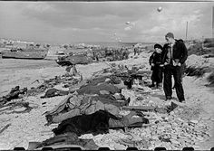 Normandy. June, 1944. French fishermen looking at the corpses of slain US soldiers on Omaha Beach. I personally think they are Seabees, because civilians had no access to the beaches.