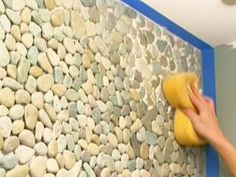 Create a dramatic focal point in a once boring bathroom by covering an entire vanity wall with pebble tile. Learn how on DIYNetwork.com.