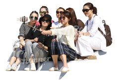 A group of asian women sitting on the stairs and taking a selfie