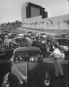 """San Francisco Drive-In Movie (1948) White uniformed """"Lot boys"""" moving amidst swarming cars as they make change & sell tickets at the main entrance to the new Rancho Drive-In Theater."""