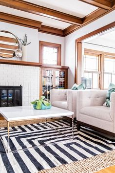 White painted brick, natural wood trim, neutral chairs, layered rugs - living room with casual, relaxed vibe: