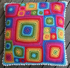 """Rainbow colored crochet pillow made of tiny and very colorful """"granny squares""""  -  flickrhivemind.net"""