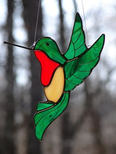 This delightful stained glass bird is hand crafted from iridescent emerald green with accent colors of red and amber. The hummingbird measures Stained Glass Night Lights, Stained Glass Ornaments, Stained Glass Birds, Stained Glass Suncatchers, Faux Stained Glass, Stained Glass Designs, Stained Glass Panels, Stained Glass Projects, Fused Glass Art