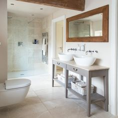 White bathroom with long rectangular mirror and twin basins