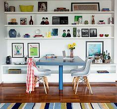 A mesa azul ganhou destaque entre as prateleiras brancas da estante que apoia o café de um lado e as bebidas do bar no outro, além dos objet...