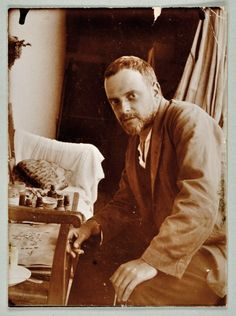 Paul Klee with the cat Fripouille in Possenhofen, Germany in 1921, alongside his work All Souls' Picture, 1921 Photo: Felix Klee