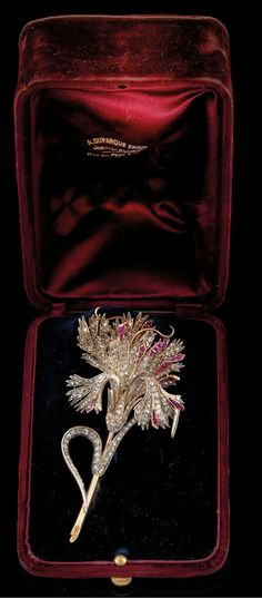 A 'carnation' diamond and ruby brooch. rosé gold 580 and silver diamond rhombs total weight c. 2.50 ct, workmanship c. 1900, 30 g, with fitted case