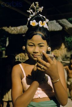 A young dancer applies the finishing touches of her makeup - . Bali, Indonesia. 1951.