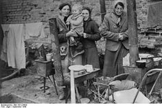 """Poland, Sept 1940, Kutno ghetto: Jewish women with young child are trying to cook who knows what in the open. The weather is already chilly. Once winter sets in, this open air """"kitchen"""" will be untenable."""