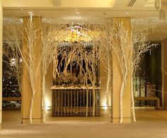 The Grove Hotel, Christmas 2009    The Silver Birch trunks were sprayed with white emulsion and then tied to the pillars. By using white cable ties, we were able to quickly create branches for the trees, using magnolia. I chose magnolia branches because they were relatively cheap and for their interesting shapes, which allowed me to 'sculpt' these trees the way I wanted.    By using cable ties, you don't need someone assisting you, as you can fix things into place very quickly.