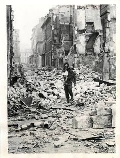British soldier carries a little French girl through bombed ruins of Caen, France, 1944