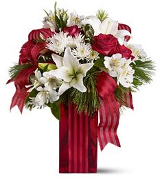 This festive mix of pure white blossoms, lush red roses and cool evergreens - presented in a bold red vase and tied up with a red striped ribbon - will be the life of any party. Let the holiday spirit move you. Send one today!