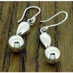 Droplet Silver Earrings: Handmade elegant pair of earrings with a touch of simple glamour. A silver ball prettily suspends from a dainty teardrop.