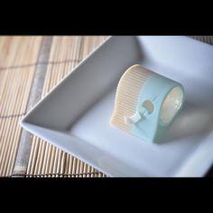 """一日一菓 「風鈴」 錦玉芯煉切巻き  wagashi of the day """"Wind chime""""  本日は「風鈴」です。 少なくとも私は見た事ないのですが、 錦玉羹を芯に煉切を巻きつけてみました。 「すだれ」と「夏空」を煉切で表現し、 風鈴の涼やかな透明感を錦玉で表現しました。 煉切の間から差し込む光が、 清涼感と風鈴を涼やかに奏でる「風」を イメージしました。 「横置き筒型」のデザインで、 芯が丸々透明なデザインは見た事がないので、 面白いかなあ?と思います。  明日は風の無い「風鈴」をご紹介します。  お楽しみに。 ※一日一菓にて御紹介している御菓子は、基本的に和菓子司いづみやにて通常店頭販売しておりません。  #和菓子 #和菓子職人 #職人 #風鈴 #Wind #あん #伝統  #japan #sweet #cake #artist  #candy  #art Japanese Food Art, Japanese Cake, Japanese Sweets, Japanese Culture, Uji Matcha, Japanese Wagashi, Candy Factory, Luxury Food, Tea Ceremony"""