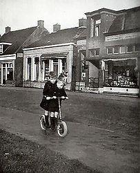 Langebuorren met winkel Atema; op autoped Johan van der Zee (links). ongeveer 1940