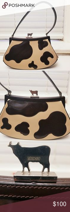 "Moschino Jeremy Scott Cow Bag Jeremy Scott / Moschino Limited Edition Cow Bag Made in Italy. measures approx 6.125"" high x 10.5"" wide x 4"" deep.  The leather strap fall length is approximately 8"".  The bag secures via silver metal Moschino signature cow press lock closure.  The interior of the bag, lined w/ Moschino signature fine textile fabric, includes a zip pocket.  The bag is in good, previously worn condition. In the case with any previously worn leather item, the leather has a couple…"
