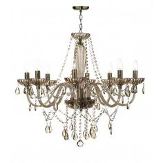 Richly decorated traditional crystal glass hanging chandelier. Supported on chrome ceiling rose and chain with frame in an attractive champagne coloured crystal glass. 8 candle style lights with chrome sleeves and removable champagne crystal sconces. Double insulated fitting.