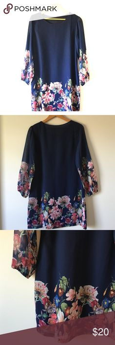 """Boutique Navy Floral Shift Dress Lovely navy shift dress with floral pattern on sleeves and around bottom. Fully lined. Sheer sleeves that hit above the wrist. Scoop neckline. Pullover style. Polyester. 20"""" pit to pit. 34"""" shoulder to bottom of hem. Purchased at a Boutique, no brand name tag. (Small snags on back of left shoulder. See photo 4). Boutique Dresses Long Sleeve"""
