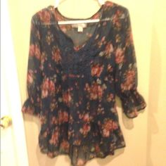 A blue floral top. Large This shirt bunches together at the elbow. It is higher in the front than the back. Git has a lace type square at the top. Great condition. Please let me know if you have questions or offers. Decree Tops Blouses