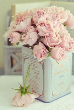 Vintage tea cans make perfect containers for pink roses! www.PamKelleyVignettes.com