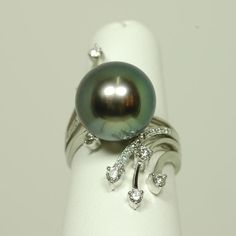 18K gold ring set with a 13.5mm Tahitian black pearl and studded with .48ct diamonds.