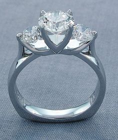 This elegant three stone diamond ring features sweeping prongs that hold a 1.10 carat center and embrace two brilliant round diamond side stones that are 0.86 carat total. 14k white gold and one of a kind.- Images Jewelers