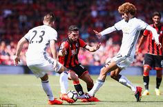 Lewis Cook (centre) tries to weave his way through the tackles of Marouane…