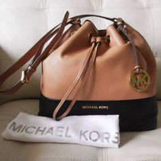 """MICHAEL KORS Jules Genuine Leather Bucket Tote Bag Colorblocked leather in Suntan / Black brings an edgy element to the luxurious Michael Kors """"Jules"""" pebbled leather bucket bag! A polished, 18K gold-plated charm details the side and drawstrings loosen the magnetic top. Features a logo-lined interior with 4 notch pockets and a zip compartment, as well as an adjustable strap with 13.5"""" drop. This is the larger size, crafted of 100% genuine cowhide leather. Very reminiscent of the Mansur…"""