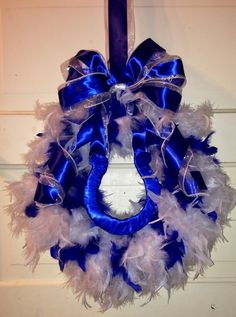 Easy Indianapolis Colts wreath. White boa from Walmart $4.97, blue boa from Dollar Tree $1.00. Horseshoe made from cardboard wrapped in $.97 blue ribbon from Walmart. On a $.10 wire hanger with a bow made from sheer white wire edged ribbon $1.00 and wide blue ribbon $1.97 both from Walmart. So less than $11.00.