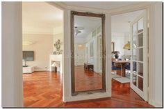 Geef de hal meer ruimte door op een blinde muur een grote spiegel te hangen