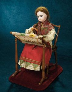 "19""~French Musical Automaton ""Lady at her Needlework"" by Roullet et Decamps~~ Marks: Depose Tete Jumeau 5 (head). Comments: Roullet et Decamps, circa 1890, the model appeared in the catalog of that firm as model 309, named ""Tapisseuse"". When wound, music plays, the doll lifts her head, turns and nods. Her fingers work busily over the needlework on frame adding stitches to the message ""Bon Joyeaux Noel"" which she is weaving onto the canvas."