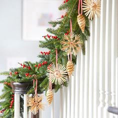 How to step up an entryway display: Embellish an evergreen garland (fresh-cut or fake) with berry branches and ornaments that resemble pinecones and snowflakes. Drape greenery along a doorway or staircase handrail, then hang ornaments from ribbon loops. #christmas #holiday #crafts