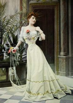 Floor-length gown with cape sleeves, corsetted bodice and circular skirt.