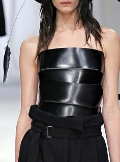 Black leather bodice with chunky banded structure; edgy fashion details // Ann Demeulemeester