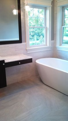 "Master Bathroom  Designer: Donna Triolo, Mid-America Tile, Elk Grove Village, ILBath Floor: Piemme PureStone Grey 12"" x 24"" Field Tile with Mapei Ultracolor Warm Gray Grout  Van Hearron Grout Once Additive. Tub Accent Wall  Wainscot: Piemme PureStone White Muretto 12"" x 24"", Florida Tile Streamline Chairrail 3/4"" x 6"" in color Arctic White. Grout: Mapei Ultracolor White with Van Hearron Grout Once Additive."