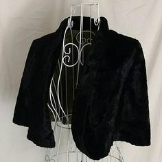 This gorgeous black velvet capelet was made by Whitley-ette - a high end mid-century designer. Though I dont know the exact date of production, the capelet is 60-70 years old. It has an avacado green lining and folds to use for your hands. The only flaw to this vintage item is some discoloration and small holes on the lining, which cannot be seen while worn. A great classic piece to keep off the chill. An open design, the capelet isnt sized. But my mannequin is 32 22 32.