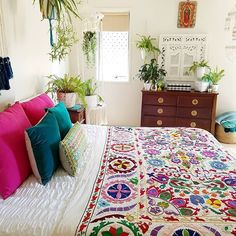 A cute and colorful boho bedroom with lots of live plants!