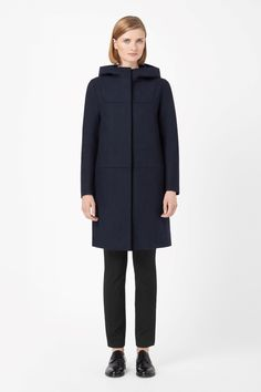 A clean straight shape, this long hooded jacket is made from panels of unlined wool. With neat fitted shoulders and slim long sleeves, it has in-seam pockets and a hidden zip fastening for a clean front. The hood is secured with two hidden press studs.