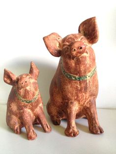 Two primitive folk art, red clay, country pigs. These clay pigs are in excellent vintage, condition and have great rough texture and nice details! The colors are a rich rust, antique spotted white with specks of an oxidized bluish black and a bit of mustard yellow here and there. There are small pin holes all around both pigs...not sure if it is part of the process but they definitely look normal and not out of place.  There is a pretty circle, green patterned collar around the pigs necks…