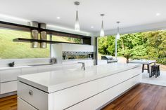 This Luxury Kitchen Design captures the view of the valley, surrounding bush and natural light by carefully positioning glass windows to act as the canvass to create this indoor outdoor Kitchen Space. Modern Kitchen Island, Kitchen Island With Seating, New Kitchen, Island Bench, Kitchen Islands, Big Island, Kitchen Jars, Kitchen Cabinets, Indoor Outdoor Kitchen