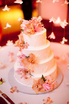 Hanging orchids surround the cake, adding drama.  Photo by James Rubio Photography.