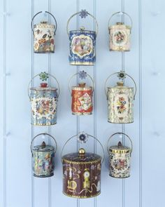 Blue Wall  Suspended from wooden pegs tipped with 1940s tin tiebacks is a bevy of covered tin pails from the 1950s and '60s, some lithographed with scenes or birds, a la hand-painted Continental porcelains, others with bouquets or all-over prints.