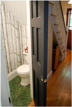 Love the wallpaper and outdoor carpet for this little under the stairs restroom.