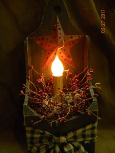 A country pimitive candle box to add some light to corner of any room. Has a metal star, pip berries, and a homespun fabric bow and a light with silcone bulb. It is 16 inches tall, 6 1/2 inches wide and 4 inches deep. Extra long cord with on/off switch.$22.00